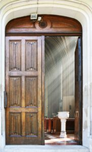 Front door of a church with light streaming inside